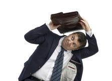 Businessman holding briefcase over head Stock Photo