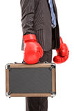 Businessman holding a briefcase with red boxer gloves Stock Photo