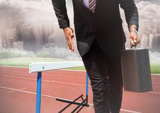 Businessman holding briefcase and running on race track royalty free stock photos