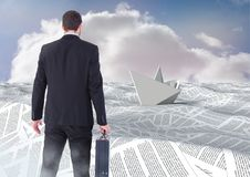 Businessman holding briefcase in sea of documents under sky clouds with paper boat Royalty Free Stock Photography