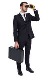 Businessman holding a briefcase while using binoculars Stock Photo