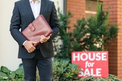 Businessman holding brown leather briefcase. Close-up of businessman in black suit holding brown leather briefcase standing next to a house for sale royalty free stock image