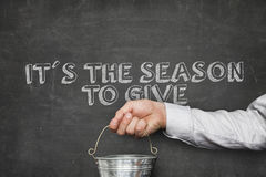 Businessman Holding Bucket By Slogan On Blackboard. Cropped image of businessman holding bucket with its the season sale to give text on blackboard Royalty Free Stock Photo