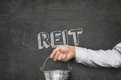 Businessman Holding Bucket Under REIT Text On Blackboard. Cropped image of businessman holding metallic bucket under REIT text on blackboard Stock Photography