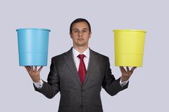 Businessman holding buckets Stock Photography