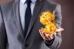 The businessman holding burning american dollar sign Stock Image