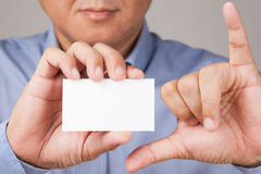 Businessman holding a business card with hand gesture. A closed up shot of a businessman holding a white blank business card with some hand gesture Royalty Free Stock Photo