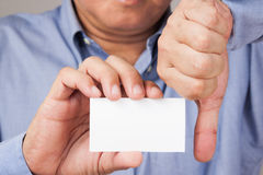 Businessman holding a business card with thumb down. A closed up shot of a businessman holding a white blank business card with his thumb pointing down Stock Photo