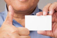 Businessman holding a business card with thumb up. A closed up shot of a businessman holding a white blank business card with thumbs up Royalty Free Stock Image