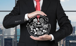 Businessman holding business symbols Royalty Free Stock Photos