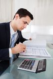 Businessman holding calculating expense in office Stock Image