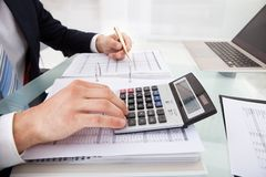 Businessman holding calculating expense in office Royalty Free Stock Photo
