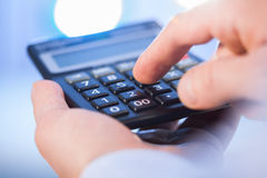 Businessman holding a calculator and counting Stock Photo