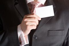 Businessman holding a card. Business card being held by man in a suit Royalty Free Stock Photography