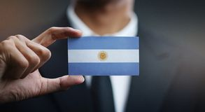 Businessman Holding Card of Argentina Flag.  royalty free stock image