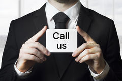 Businessman holding card call us. Businessman in black suit holding card call us Royalty Free Stock Photo