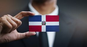 Businessman Holding Card of Dominican Republic Flag.  stock photography