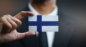 Businessman Holding Card of Finland Flag.  stock photos