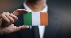 Businessman Holding Card of Ireland Flag.  stock photo