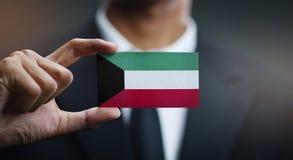 Businessman Holding Card of Kuwait Flag royalty free stock image
