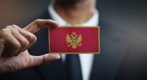 Businessman Holding Card of Montenegro Flag royalty free stock photos