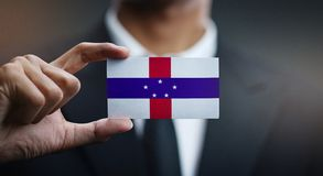 Businessman Holding Card of Netherlands Antilles Flag.  royalty free stock images