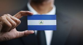 Businessman Holding Card Nicaragua Flag.  stock photography