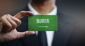 Businessman Holding Card of Saudi Arabia Flag.  stock photography