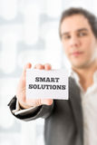 Businessman Holding a Card with Smart Solutions Stock Image