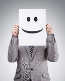 Businessman holding card with smiley face Stock Image