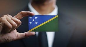 Businessman Holding Card of Solomon Islands.  stock photo