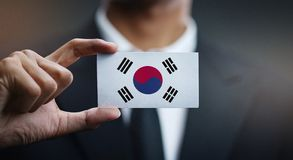 Businessman Holding Card of South Korea Flag.  stock photos