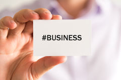 Businessman holding a card with text BUSINESS Royalty Free Stock Photos