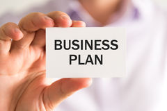 Businessman holding a card with text BUSINESS PLAN Royalty Free Stock Photography
