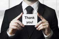 Businessman holding card thank you. Businessman in black suit holding small white card thank you Royalty Free Stock Photo