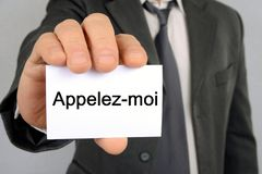 Businessman holding a card on which is written in French call me royalty free illustration