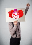 Businessman holding a cardboard with a clown on it in front of h Royalty Free Stock Photos