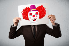 Businessman holding a cardboard with a clown on it in front of h Stock Images