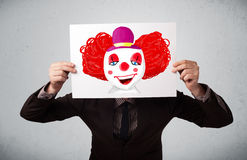 Businessman holding a cardboard with a clown on it in front of h Royalty Free Stock Images