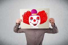 Businessman holding a cardboard with a clown on it in front of h Royalty Free Stock Photo