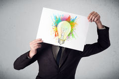 Businessman holding a cardboard with paint splashes and lightbul Royalty Free Stock Image