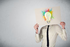Businessman holding a cardboard with paint splashes and lightbul Royalty Free Stock Images