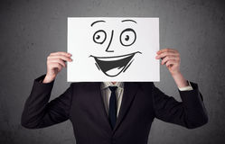 Businessman holding a cardboard with smiley face on it in front Royalty Free Stock Photos