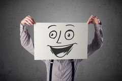 Businessman holding a cardboard with smiley face on it in front Royalty Free Stock Photography