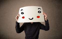 Businessman holding a cardboard with a smiley face on it Stock Photo