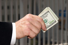 Businessman holding cash. A businessman handing over a wad of cash Stock Photo