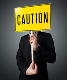 Businessman holding a caution sign Stock Image
