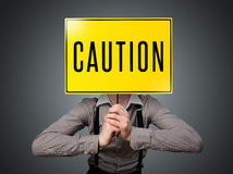 Businessman holding a caution sign Stock Images