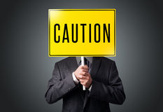 Businessman holding a caution sign Royalty Free Stock Photography