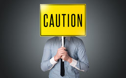 Businessman holding a caution sign Stock Photography
